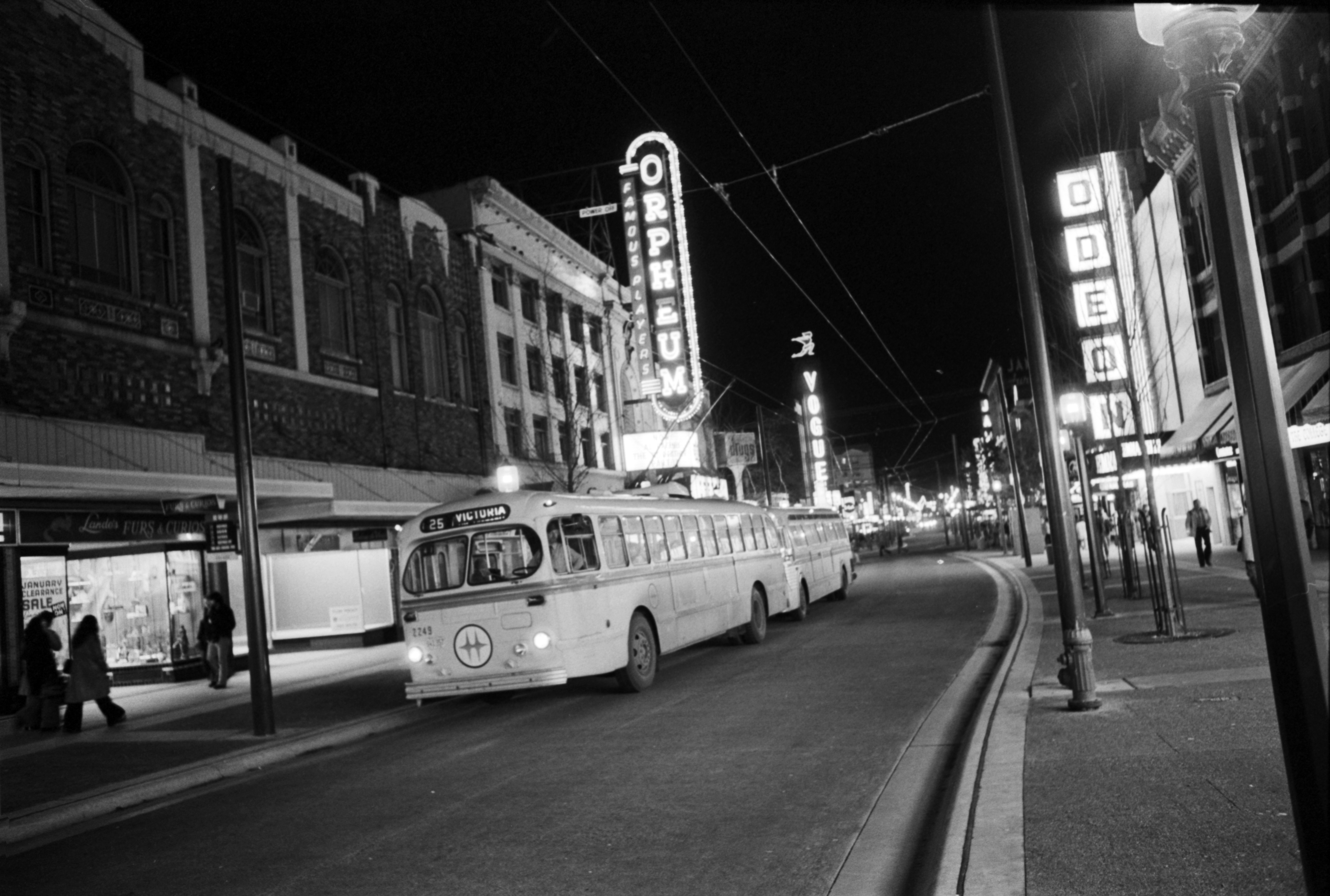 With electric trolley buses and neon signs as a backdrop, Granville Street glows at night. January 3, 1975. Ralph Bower/Vancouver Sun (75-0026)